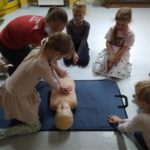uczennica pod kierunkiem nauczyciela dokonuje ucisku klatki piersiowej na fantomie troje pozostałych uczniów przygląda się